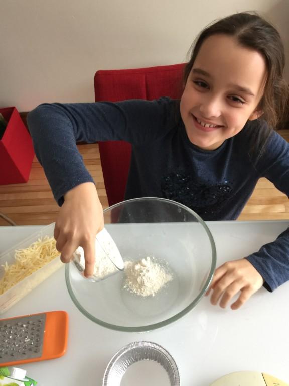 Louison pèse la farine pour les mini-quiches